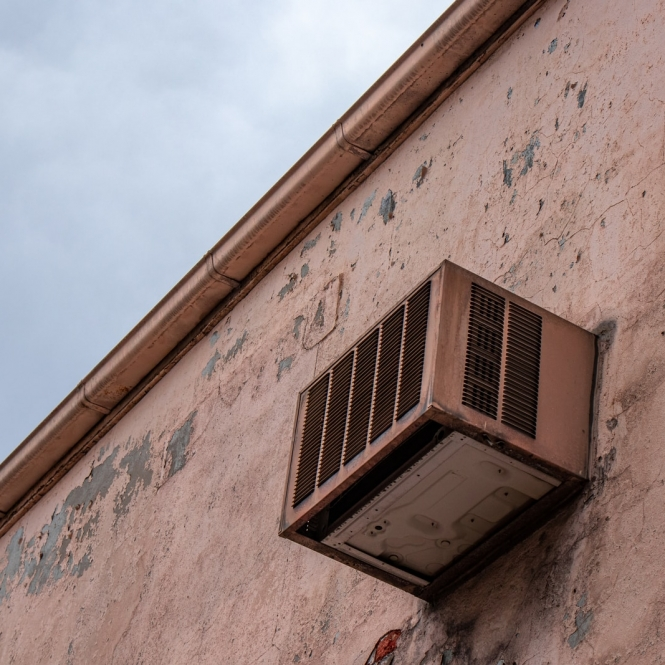 gray window-type AC unit during daytime