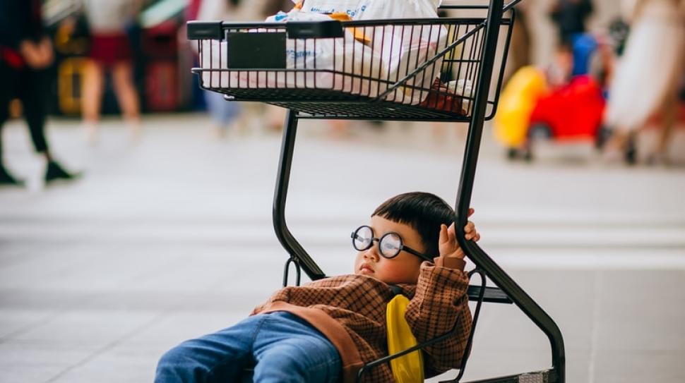 boy in orange jacket sitting on black shopping cart